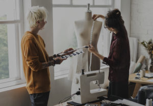 Fashion designer using a measuring tape on a mannequin